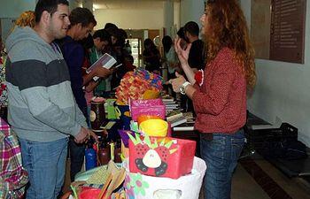 Un grupo de alumnos realiza sus compras en el mercadillo solidario en la Facultad de Letras.