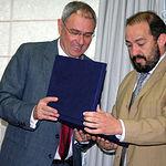 El rector de la UCLM, Ernesto Martínez Ataz, durante la entrega de una placa conmemorativa a Julián Garde por su prolífica carrera investigadora.