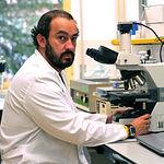 Julián Garde examinando unas muestras de semen al microscopio.
